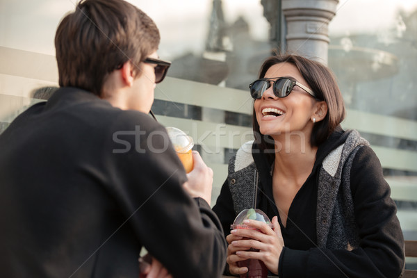 Laughing young lady sitting outdoors with her brother Stock photo © deandrobot