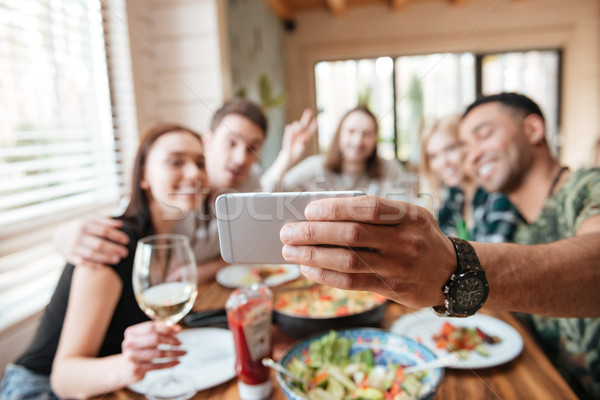 Group of friends eating and taking selfie at the table Stock photo © deandrobot