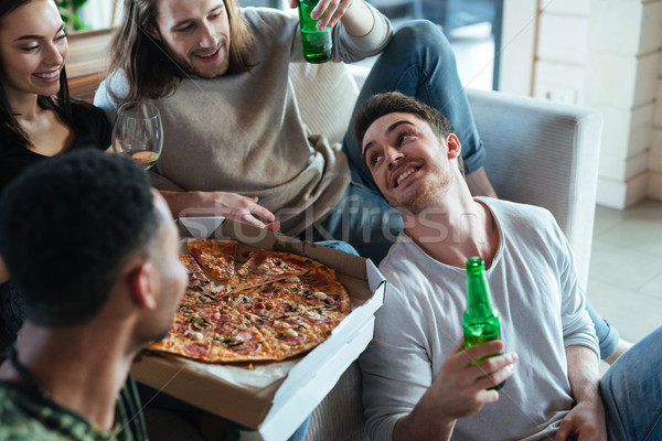 Cropped image of four friends sitting with pizza Stock photo © deandrobot