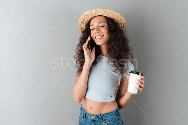 Pleased curly woman in hat talking by the smartphone Stock photo © deandrobot