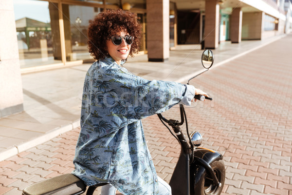 Back view of happy woman in sunglasess sitting on motorbike Stock photo © deandrobot