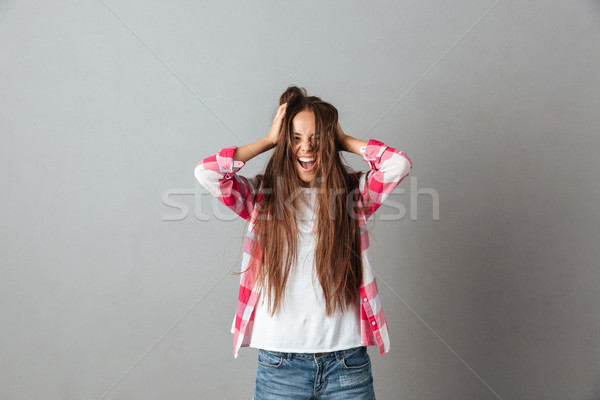 Photo of young long haired woman screaming and touching hair Stock photo © deandrobot