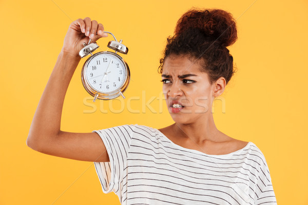 Displeased african woman holding alarm clock and looking on them Stock photo © deandrobot
