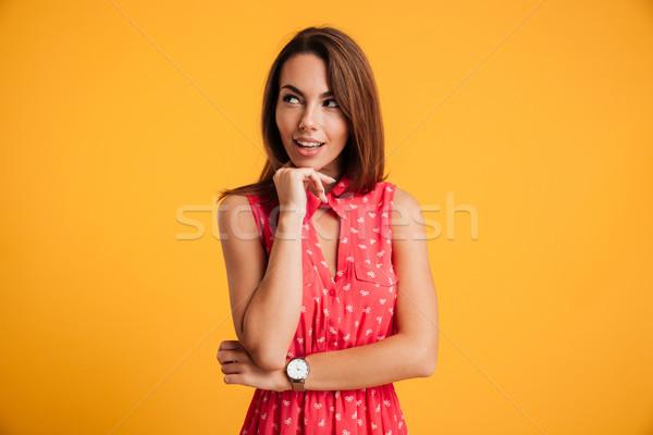 Foto sorridente mulher jovem vestido vermelho tocante queixo Foto stock © deandrobot