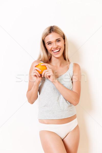 Portrait of a happy fit girl in underwear orange fruit Stock photo © deandrobot
