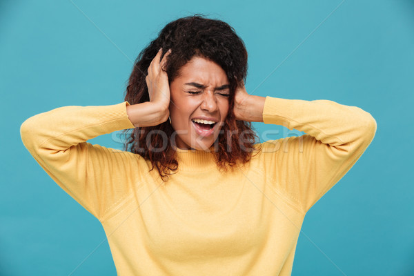 Angry african woman in sweater screaming and covering her ears Stock photo © deandrobot
