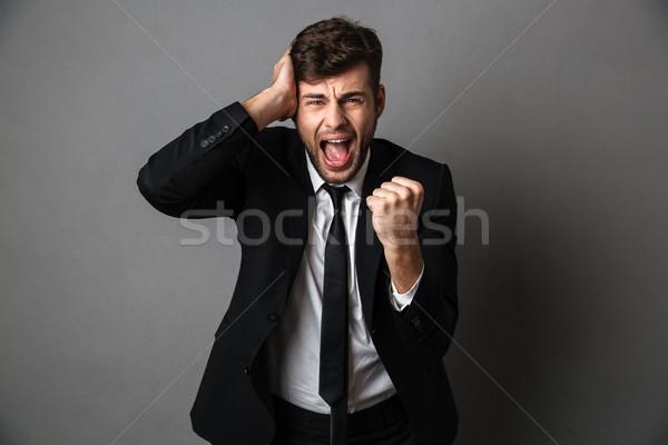 Foto boos schreeuwen jonge man zwart pak Stockfoto © deandrobot