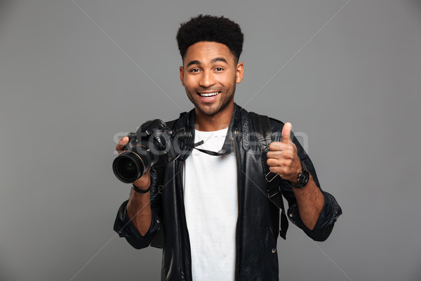 Young smiling afro american man holding photocamera and showing  Stock photo © deandrobot
