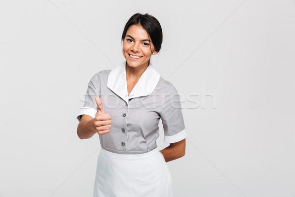 Vrolijk brunette huishoudster uniform tonen duim Stockfoto © deandrobot