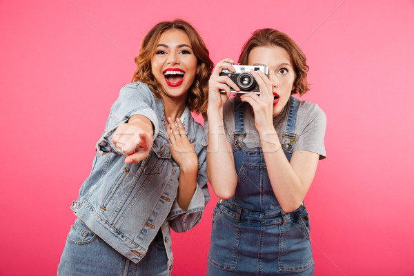 Happy ladies make photo by camera and pointing to you. Stock photo © deandrobot