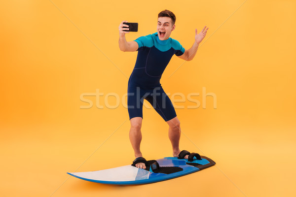 Full length photo of cheerful man surfing while taking selfie on Stock photo © deandrobot
