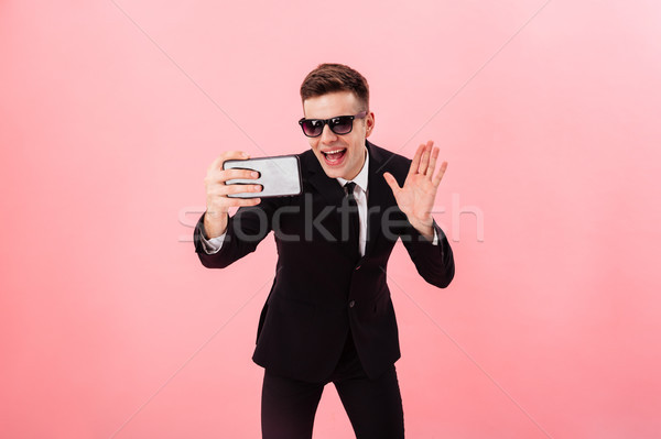 Funny man in sunglasses and suit making videocall Stock photo © deandrobot