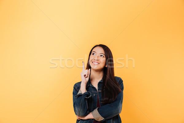 Glimlachend asian vrouw denim jas wijzend Stockfoto © deandrobot