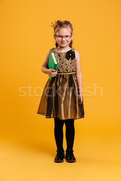 Cute girl child wearing princess crown reading book. Stock photo © deandrobot