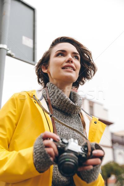 Koncentrált fiatal hölgy fotós kép esőkabát Stock fotó © deandrobot