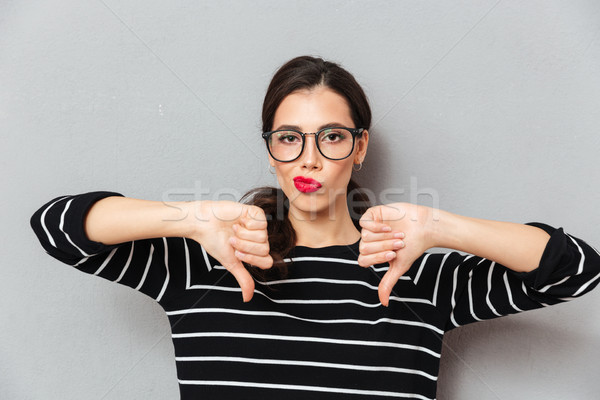 Stock photo: Portrait of a unsatisfied woman in eyeglasses
