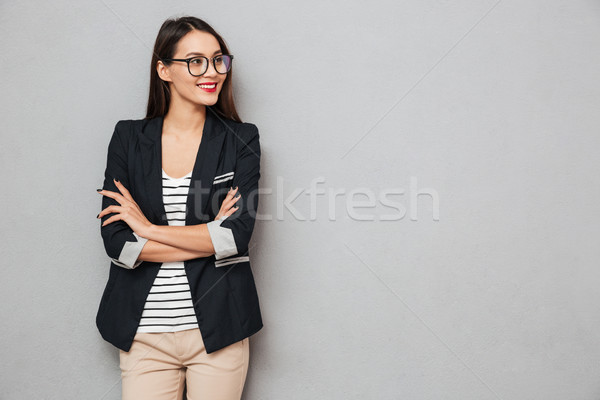 Smiling business woman in eyeglasses with crossed arms looking away Stock photo © deandrobot