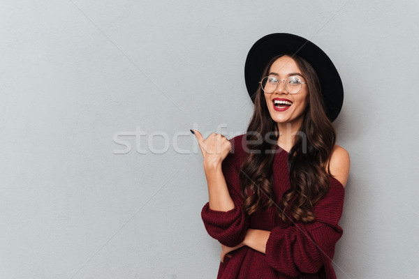 Young beautiful hipster girl showing thumb up gesture, looking a Stock photo © deandrobot