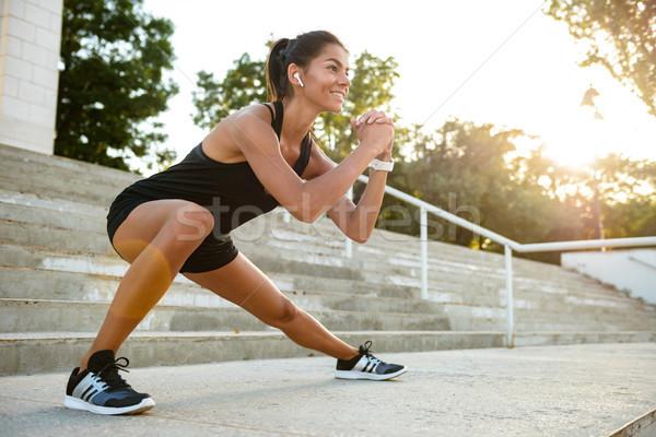 Portré mosolyog fitnessz nő fülhallgató nyújtás lépcsősor Stock fotó © deandrobot