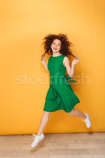 Full length portrait of a happy redhead woman in dress Stock photo © deandrobot