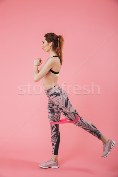 Vertical side view image of concentrated sportswoman doing fitness exercise Stock photo © deandrobot