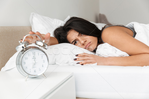Image of dissatisfied woman 20s lying in bed on pillow, and turn Stock photo © deandrobot