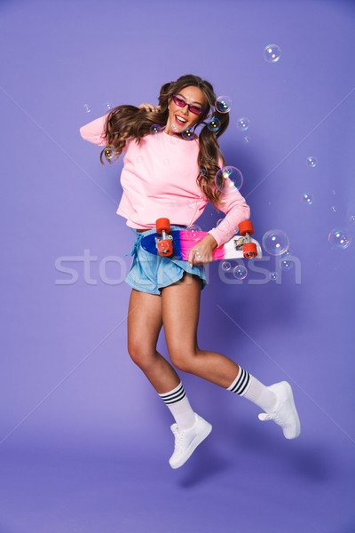 Full length portrait of a cheerful girl in sweatshirt Stock photo © deandrobot