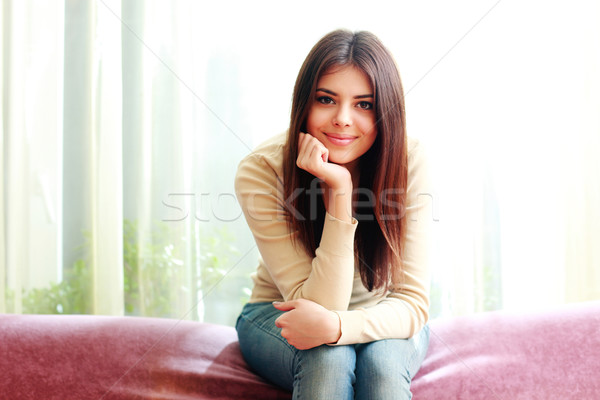 Young beautiful happy woman sitting on the sofa at home Stock photo © deandrobot