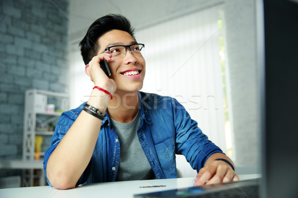 Young happy asian man talking on the phone at his workplace in office Stock photo © deandrobot