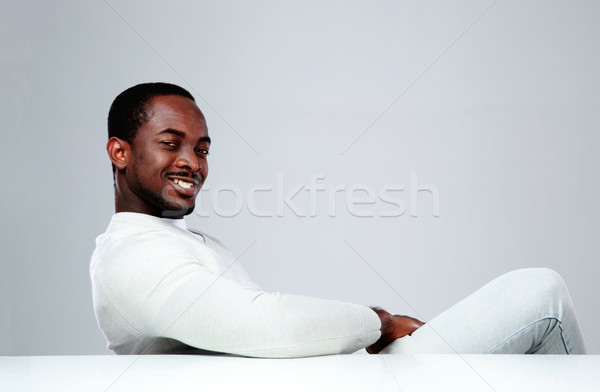 Cheerful african man sitting at the table on gray background Stock photo © deandrobot