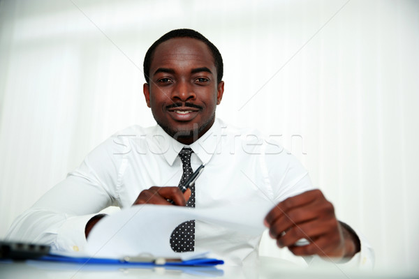 Happy african man sitting at the table and signing document in office Stock photo © deandrobot