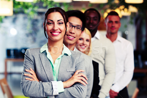 Happy group of business people in the office lined up Stock photo © deandrobot