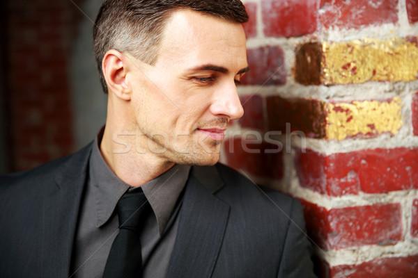 Closeup portrait of a thoughtful businessman near brick wall Stock photo © deandrobot