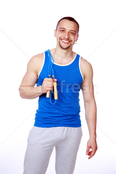 Happy sportsman standing with jumping rope over white background Stock photo © deandrobot