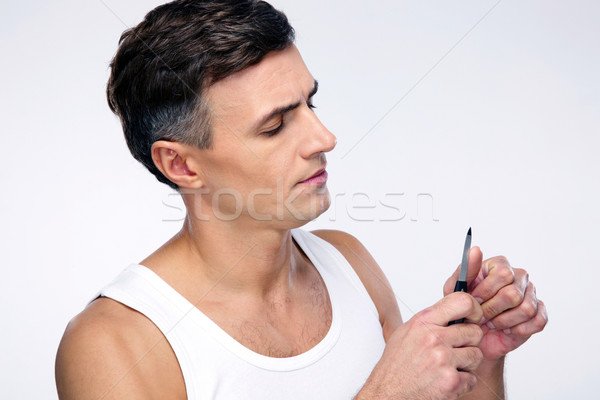 Man doing manicure over gray background Stock photo © deandrobot