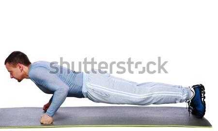 Muscular man exercising on exercise mat over white background Stock photo © deandrobot