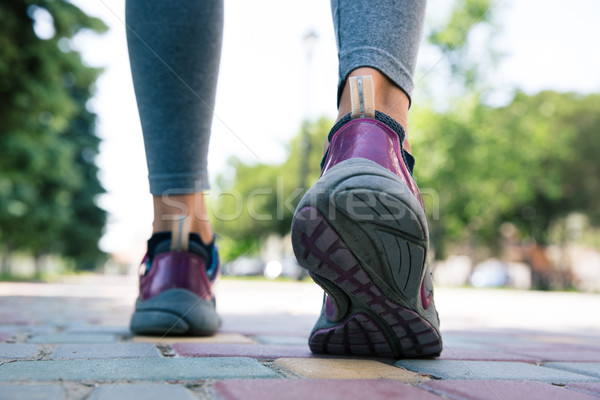 Footwear on female feet running on road  Stock photo © deandrobot