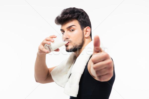 Fitness man drinking milk Stock photo © deandrobot