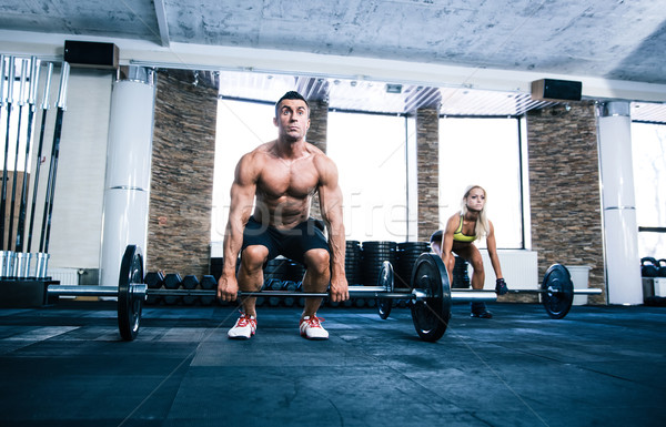 Group of woman and man workout with barbell Stock photo © deandrobot