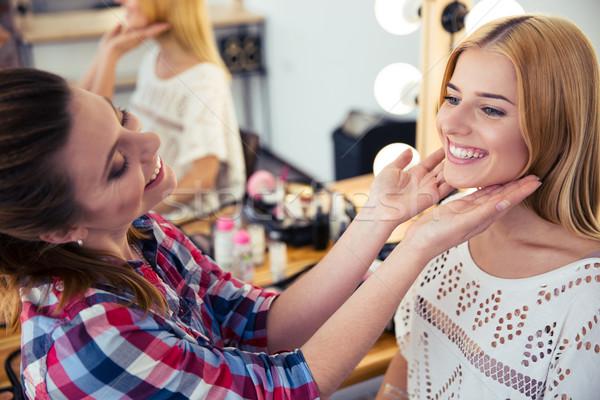 Visagist looking at woman`s makeup in salon Stock photo © deandrobot