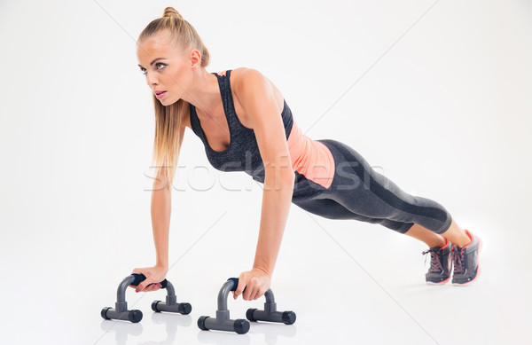 Portrait of a fitness woman doing push ups Stock photo © deandrobot