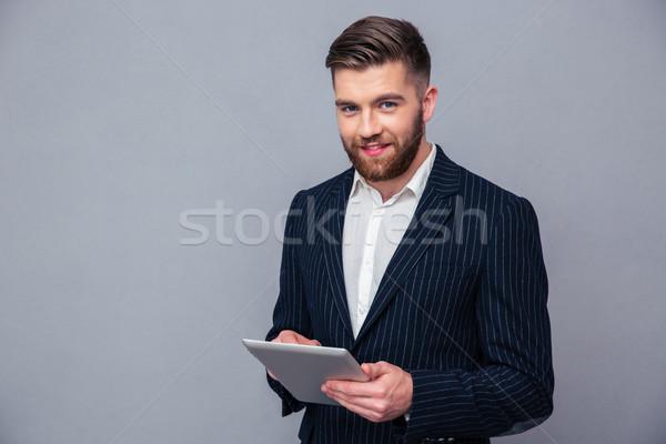 Happy businessman using tablet computer Stock photo © deandrobot