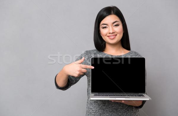 женщину указывая пальца портативного компьютера экране портрет Сток-фото © deandrobot