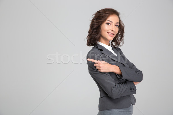 Pretty happy woman crossed arms and pointing away on copyspace Stock photo © deandrobot