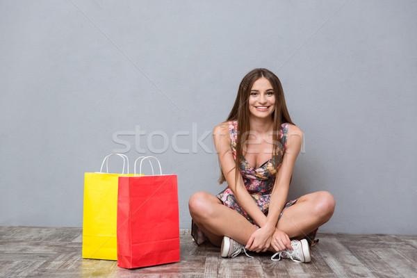 Gyönyörű mosolyog lány ül padló lábak keresztbe Stock fotó © deandrobot