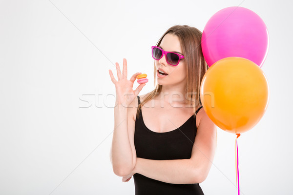 Amusing young woman in pink sunglasses eating macaroons Stock photo © deandrobot