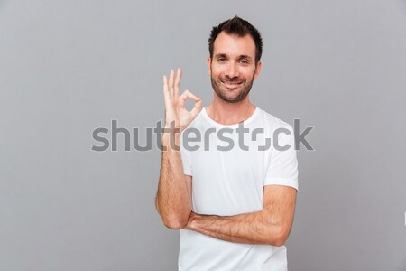 Handsome inspired male pointing away on copyspace Stock photo © deandrobot
