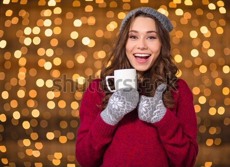 Closeup of cup with candy cane holded by smiling female  Stock photo © deandrobot