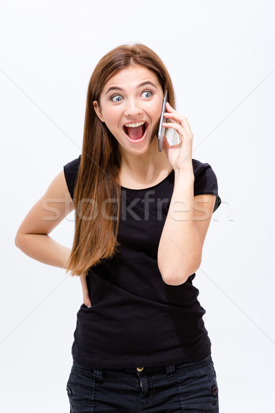 Cheerful excited young woman talking on cell phone Stock photo © deandrobot