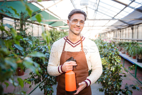 Attractive male gardener standing and holding water pulveriser  Stock photo © deandrobot